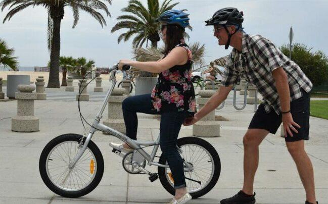 The first time cycling needs a hand to help to balance.
